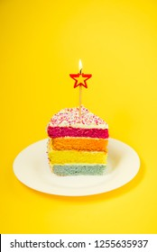 Slice of Rainbow cake with birning candle in the shape of star on white round plate isolated on bright yellow background. Happy bithday, party concept. Vertical card. Selective focus. Copy space