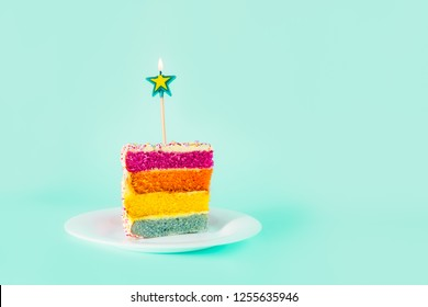 Slice of Rainbow cake with birning candle in the shape of star on white round plate isolated on turquoise background. Happy bithday, party concept. Selective focus. Copy space