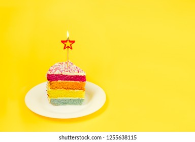 Slice of Rainbow cake with birning candle in the shape of star on white round plate isolated on bright yellow background. Happy bithday, party concept. Selective focus. Copy space