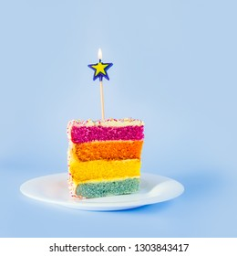 Slice of Rainbow cake with birning candle in the shape of star on white round plate isolated on blue background. Happy bithday, party concept. Square card. Selective focus. Copy space