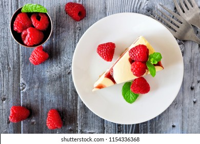 Slice of raspberry cheesecake on a plate, top view scene over a rustic gray wood background