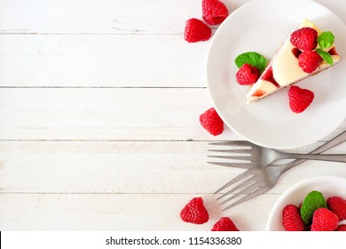 Slice of raspberry cheesecake, top view on a white wood background. Side border with copy space.