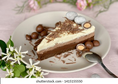Slice of raw ketogenic cake with three different chocolate layers on a plate, decorated with confetti and flowers. Healthy diet concept. Pink wedding concept. Selective focus, shallow dof. Horizontal.