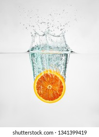 a slice of red orange falls into the water discarding a lot of splashes and drops.