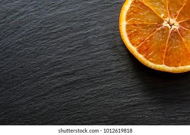 Slice of red orange on black background, selective focus, copy space
