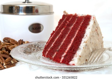 Slice of red velvet cake closeup with sliced pecans and sugar canister in background.  Cake is on plate along with fork.  Isolated on white background.