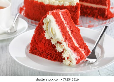 a slice of red velvet cake topped with beautiful creamy roses on plate on wooden table with cup of tea and whole cake at background,  view from above, close-up