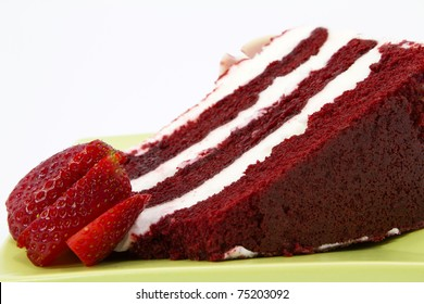 A slice of red velvet cake with white frosting is garnished with strawberries and placed on a square, green plate; close up; white background;