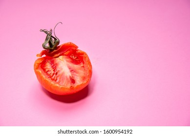 Slice or rotten red tomato vegetable  isolated on a magenta background