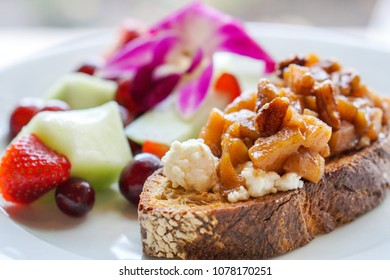 Slice of Rustic Toast Topped with Cheese, Spiced Apples, and Walnuts Served with Fresh Fruit