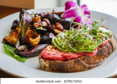Slice of Rustic Toast Topped with Fresh Avocado Slices, Beet Hummus, and Sprouts Served with Green Salad
