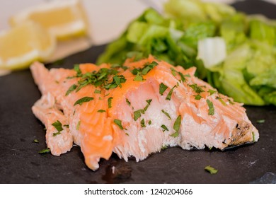 A slice of salmon barbecue. Background: green salad and lemon.