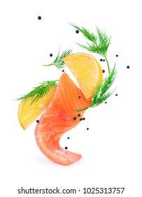 Slice of salmon with slices of lemon and spices in dynamic motion on white background