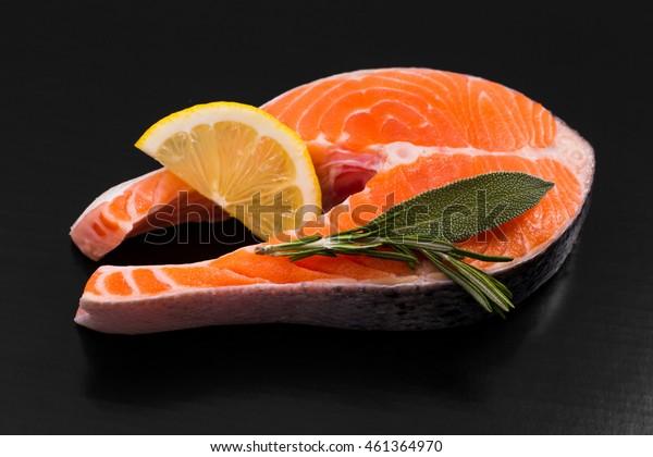 Slice of salmon steak with lemon and herbs on black