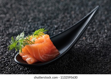 Slice of salted salmon with dill on the background of black sesame.