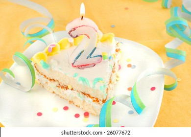 slice of second birthday cake with lit candle, confetti, and ribbon