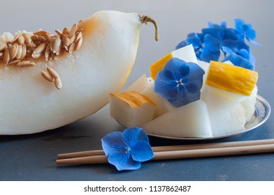slice with the seeds of a white melon, ice and melon cubes with blue flowers on the saucer