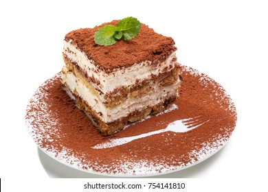 Slice of self-made italian tiramisu dessert served on a plate isolated on white