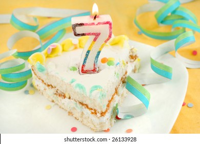slice of seventh birthday cake with lit candle, confetti, and ribbon (shallow depth of field)