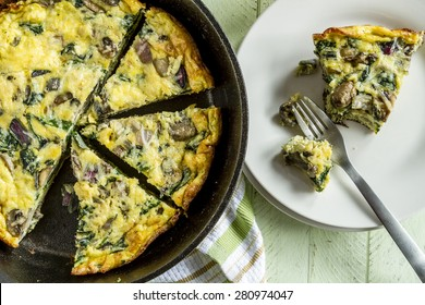 Slice of a spinach mushroom frittata sitting on white plate and fork next to cast iron skillet pan