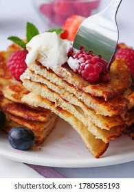 Slice of stacked keto pancakes made of coconut flour or almond flour, served with berries on fork, vertical.