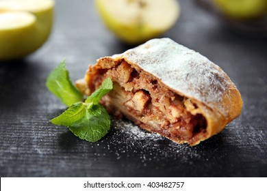 Slice of strudel with apples, walnut and raisins on dark wooden table