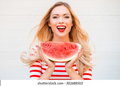 Slice of summer goodness. Beautiful young woman holding slice of watermelon and smiling while standing outdoors