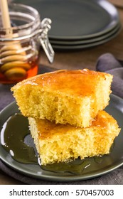 Slice of sweet cornbread with honey on the plate.