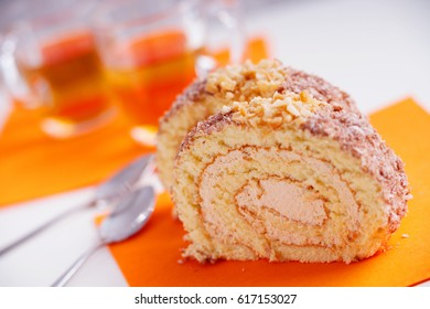 Slice of sweet cream roll and metal spoons