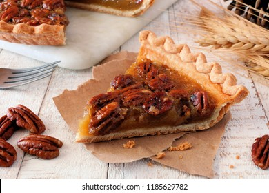Slice of sweet pecan pie. Close up table scene with a white wood background.