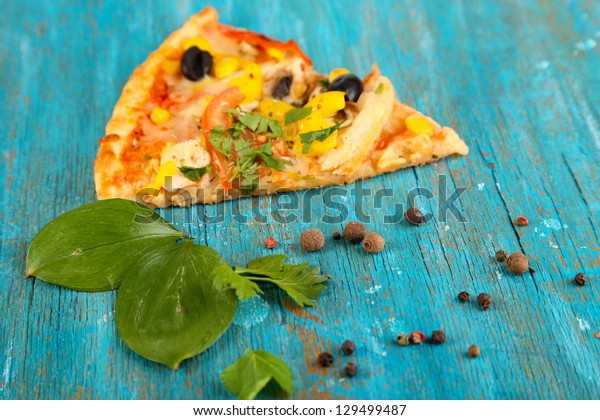Slice of tasty pizza on blue wooden table close-up