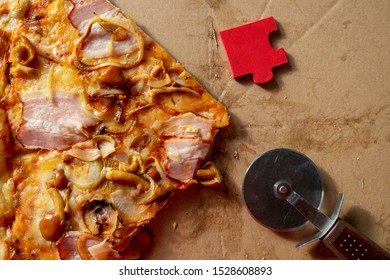 Slice of tasty traditional Italian pizza with pastry wheel and bright red puzzle piece on a marble counter in a conceptual image