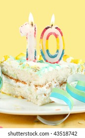slice of tenth birthday cake with lit candle, confetti, and ribbon (shallow depth of field)