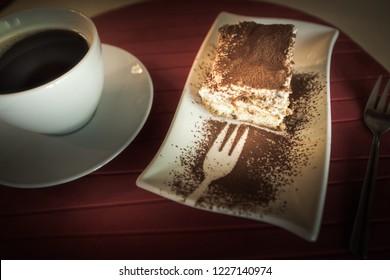 Slice of Tiramisu Cake and a cup of coffee