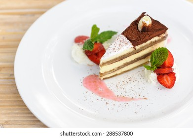 A slice of tiramisu cake served with strawberries.