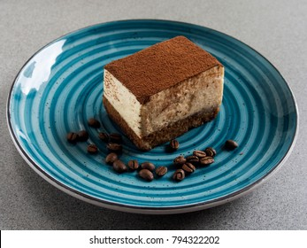 Slice of tiramisu on blue plate on grey background
