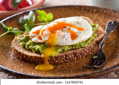 A slice of toast with delicious avocado, fried egg and hot sauce.