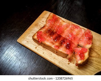 Slice of toast with red rose jam on top over wooden background. The easy and simple dish for breakfast.
