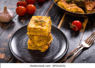 Slice of tortilla de patatas on a black plate. Traditional spanish dish with garlic sauce aioli and fresh tomatoes cherry. Omelette with eggs, potatoes and onion. Rustic black background