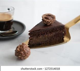 Slice of vegan Austrian Sachertorte on a golden cake cutter