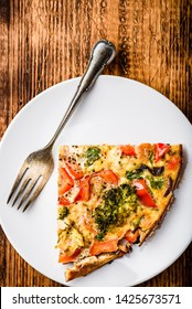 Slice of vegetable frittata with broccoli, red bell pepper and red onion on white plate. View from above