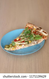 Slice of vegetarian pizza on a turquoise plate. Selective focus.