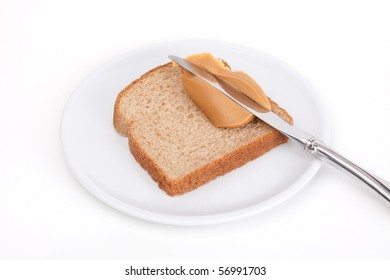 A slice of wheat bread with a knife spreading a glob of peanut butter. White background.