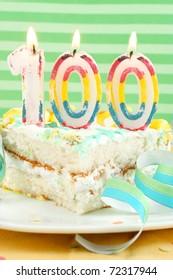 Slice of white cake celebrating 100 year birthday or anniversary on colorful background