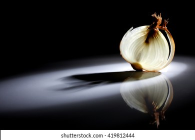 Slice of white onion on a black background with a beautiful back light.
