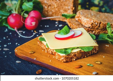 Slice of Whole Grain Bread with cheese, salat and radish on wooden board