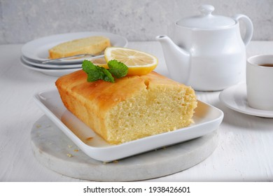 Slice and whole Lemon pound cake with white teapot and a cup of coffee with blury background,white background