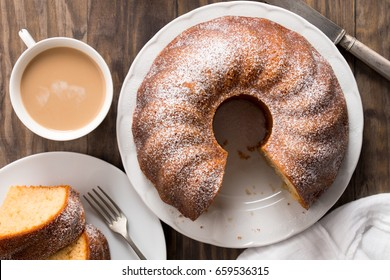 Slice of yogurt bundt cake served with a cup of coffee with milk. Top view