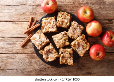 Sliced apple blondies with cinnamon and nuts close-up on a slate board on the table. horizontal top view from above