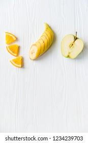 Sliced apple, orange and banana on white